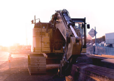 Digger parked on the side of the road in front of some aluminium beams at sunrise