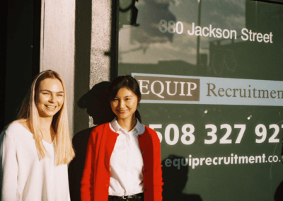 Two young woman standing and smiling in front of a window that says Equip Recruitment
