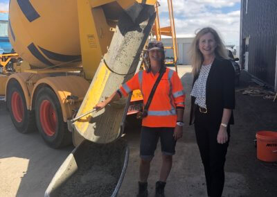 Two people stand in front of a concrete mixer smiling