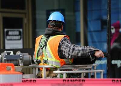 A man in a high vis vest with a blue helmet working on a construction site
